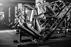 Mulher que faz o treinamento da aptidão em uma máquina do impulso da extensão do pé com pesos Imagem de Stock Royalty Free