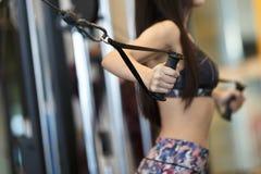 Mulher que faz o treinamento do músculo no gym Atleta que dá certo no borrão da aptidão do gym imagem de stock