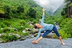 Mulher que faz o trikonasana de Utthita do asana da ioga de Ashtanga Vinyasa Fotografia de Stock Royalty Free