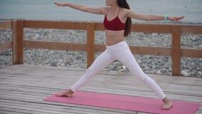 Mulher que faz a pose do guerreiro na praia filme