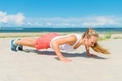 Mulher que faz push-ups Fotos de Stock Royalty Free