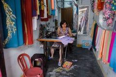 Mulher que faz a roupa na oficina em Hoi An Fotografia de Stock