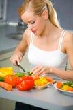 Mulher que faz a salada na cozinha Foto de Stock Royalty Free