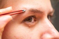 Mulher que faz seus eyebows foto de stock