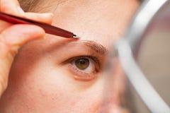Mulher que faz seus eyebows fotografia de stock royalty free