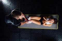 A mulher que faz triturações abdominais pressiona o exercício na esteira com seu instrutor do homem dos esportes foto de stock royalty free