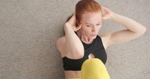 A mulher que faz triturações transversais exercita em casa vídeos de arquivo