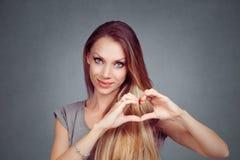 Mulher que faz um gesto do coração com suas mãos dos dedos imagens de stock royalty free