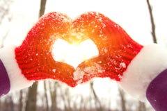 Mulher que faz um símbolo do coração com mãos da neve em luvas vermelhas fotografia de stock royalty free