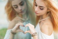 Mulher que faz uma forma do coração Imagens de Stock Royalty Free
