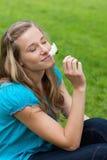 Mulher que fecha seus olhos ao cheirar uma flor Foto de Stock