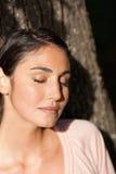Mulher que fecha seus olhos ao sentar-se contra uma árvore como o sol s Imagens de Stock Royalty Free