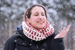 Mulher que fecha seus olhos e que sorri com mão acima como o ge das quedas da neve Fotos de Stock