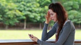 Mulher que fica irritado e irritada após ter recebido o texto video estoque
