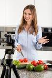 Mulher que filma sua preparação da refeição Imagem de Stock