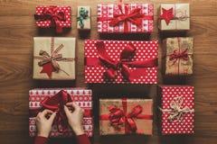 Mulher que fixa uma curva em presentes de Natal beautifuly envolvidos do vintage no fundo de madeira Imagens de Stock Royalty Free