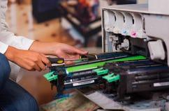 Mulher que fixa uma fotocopiadora durante a manutenção usando uma chave de fenda Imagem de Stock
