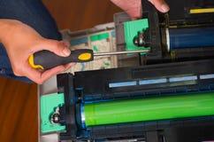 Mulher que fixa uma fotocopiadora e que sorri durante a manutenção usando uma chave de fenda Foto de Stock