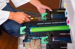 Mulher que fixa uma fotocopiadora e que sorri durante a manutenção usando uma chave de fenda Imagem de Stock