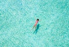 Mulher que flutua em águas tropicais foto de stock royalty free
