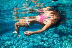 Mulher que flutua na água tropical Fotos de Stock