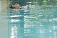 Mulher que flutua na piscina foto de stock