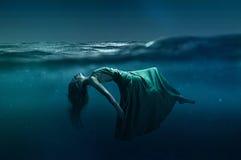 Mulher que flutua sob a água