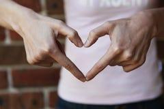 Mulher que forma a forma do coração com suas mãos fotografia de stock royalty free