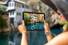Mulher que fotografa a casa na mola do Buna em Blagaj Fotografia de Stock Royalty Free