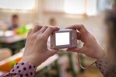 Mulher que fotografa com um interior e um pessoa idosos da câmera dentro a exposição mostra que ` s na sala Imagens de Stock