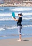 Mulher que fotografa a costa e o mar Mediterrâneo e a ressaca imagem de stock royalty free