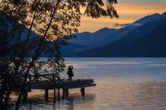 Mulher que fotografa um por do sol dramático no crescente do lago, Washington foto de stock royalty free