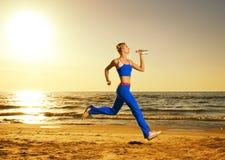 Mulher que funciona em uma praia Imagens de Stock Royalty Free