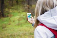 Mulher que geocaching na floresta e que usa o mapa app no smartphone Fotografia de Stock Royalty Free