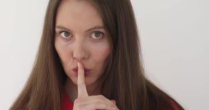 Mulher que gesticula o dedo do silêncio nos bordos vídeos de arquivo