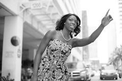 Mulher que graniza um táxi Imagem de Stock