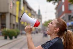 Mulher que grita em um megafone imagens de stock royalty free
