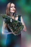 Mulher que guarda a árvore dos christmass Imagens de Stock