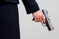 Mulher que guarda a arma da mão no fundo branco Foto de Stock