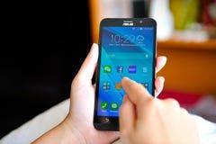 Mulher que guarda Asus brandnew Zenfone 2 Foto de Stock Royalty Free