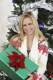Mulher que guarda atual em Front Of Christmas Tree Fotografia de Stock