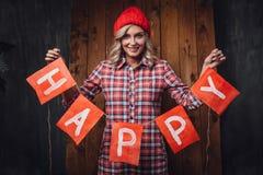 Mulher que guarda bandeiras vermelhas das letras felizes, tema do Natal Fotos de Stock Royalty Free