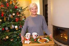 Mulher que guarda a bandeja de cookies do Natal fotografia de stock royalty free