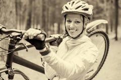 Mulher que guarda a bicicleta em seu ombro Fotografia de Stock