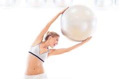 Mulher que guarda a bola do exercício Fotografia de Stock Royalty Free