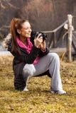 Mulher que guarda a câmera e que toma a foto fora fotografia de stock royalty free