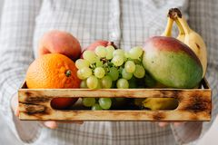 Mulher que guarda a caixa com frutos nas mãos Fotos de Stock
