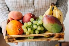 Mulher que guarda a caixa com frutos nas mãos Foto de Stock Royalty Free