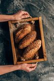 mulher que guarda a caixa de madeira com os loafs de pão nas mãos Fotografia de Stock Royalty Free
