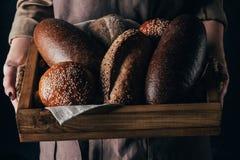 mulher que guarda a caixa de madeira com os loafs de pão nas mãos Imagens de Stock Royalty Free